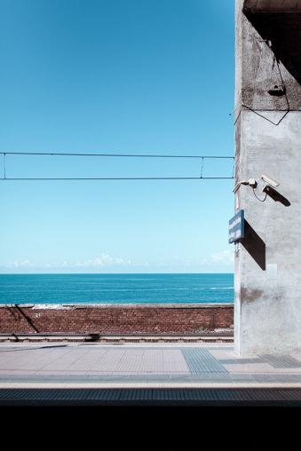 Blick auf Meer mit Straße und Hauswand im Vordergrund.