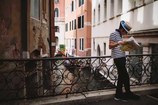 Mann auf einer Brücke liest eine Zeitung.