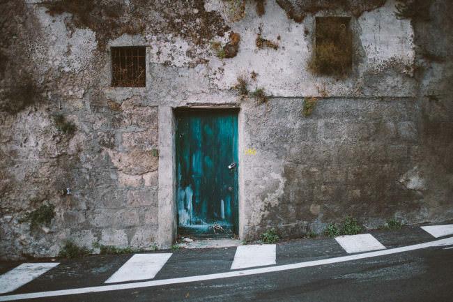 Hauswand mit türkiser Tür.