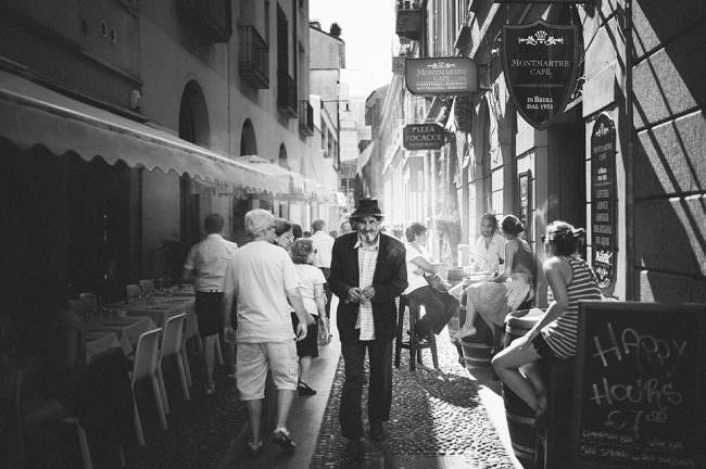 Mann mit Zigarette läuft durch eine belebte Straße.