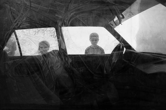Ein Auto und Schatten zweier Kinder.