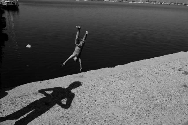 Ein ins Wasser springender Junge und ein Schatten, der nicht dazu gehört.