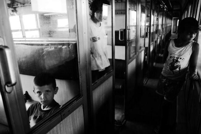 Jungs in einem Zugabteil schauen zur Fotografin.
