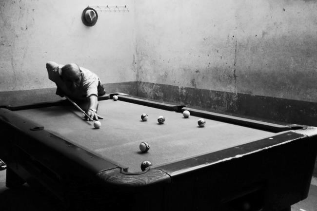 Ein Mann beim Billard spielen.