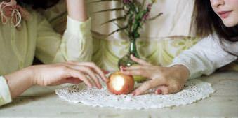 Zwei Frauen schieben sich mit den Fingerspitzen einen Apfel zu.