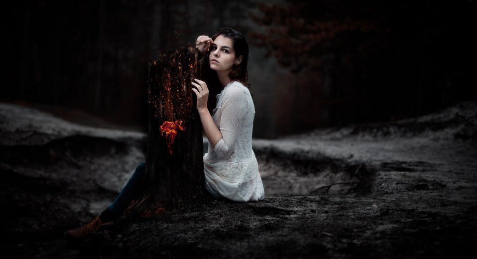 Ein Mädchen an einem Baumstumpf aus dessen Innerem Feuer lodert.