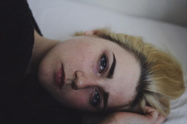 Junge Frau auf dem Bett liegend.