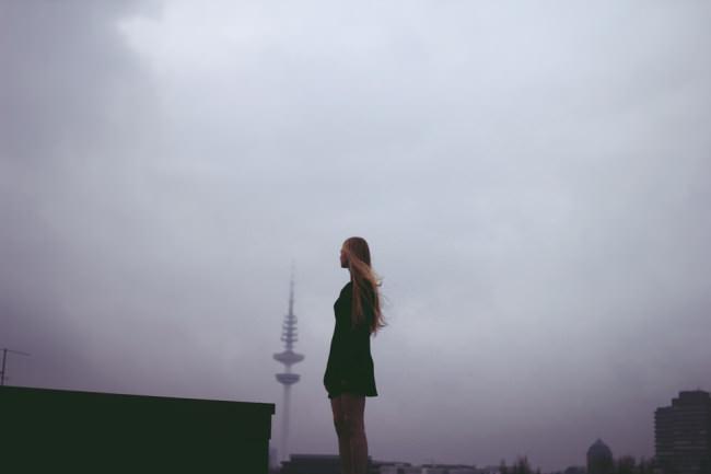 Frau auf einem Dach stehend und in die Ferne sehend.