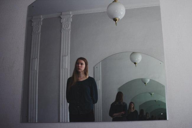 Eine junge Frau steht vor einem Spiegel in dem sich verschiedene Spiegel und sie selbst immer wieder spiegeln.