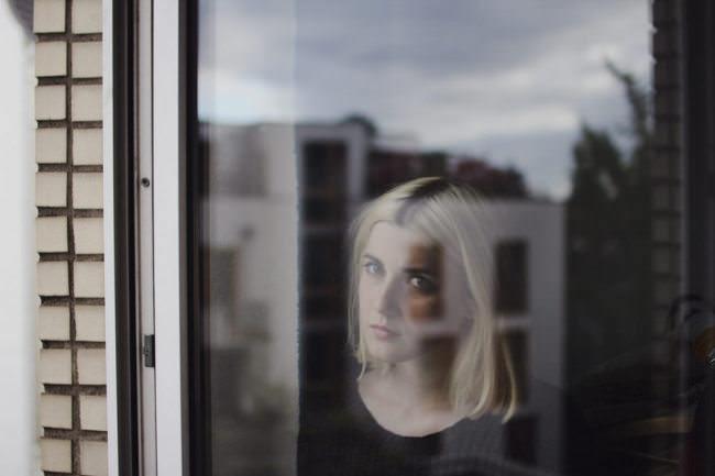 Junge Frau hinter einer Fensterscheibe.