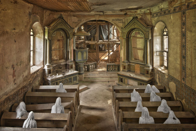 Gips-Geister auf Kirchbänken sitzend von oben fotografiert.