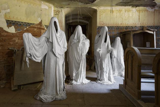 Vier stehende Geister vor einem Eingang.