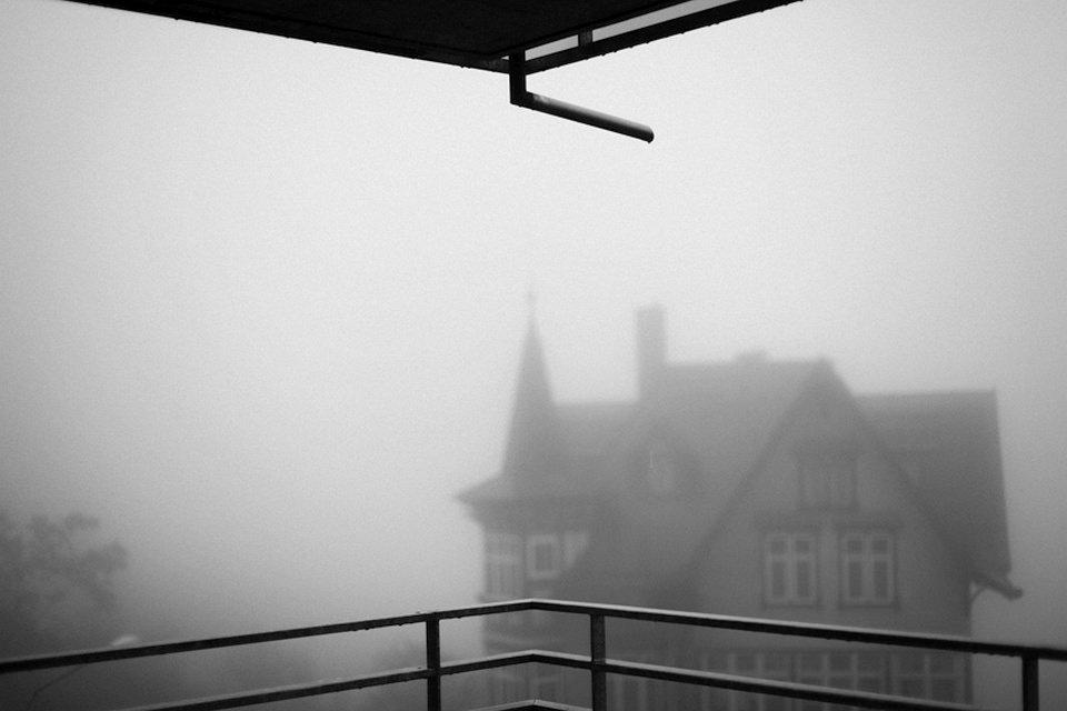 Haus mit Zinnen in dichtem Nebel, gesehen von einem Balkon.