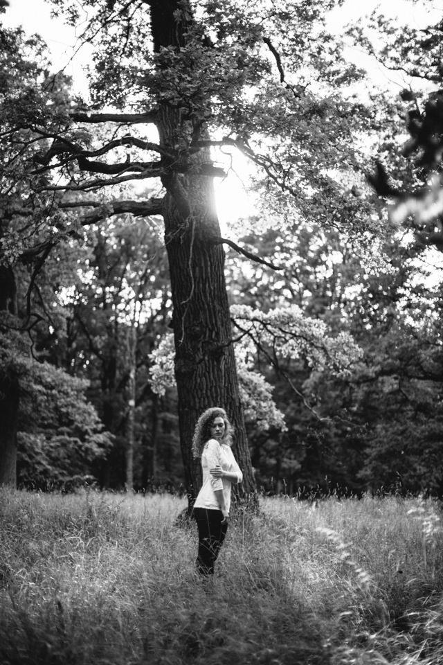 Eine Frau steht vor einem Baum