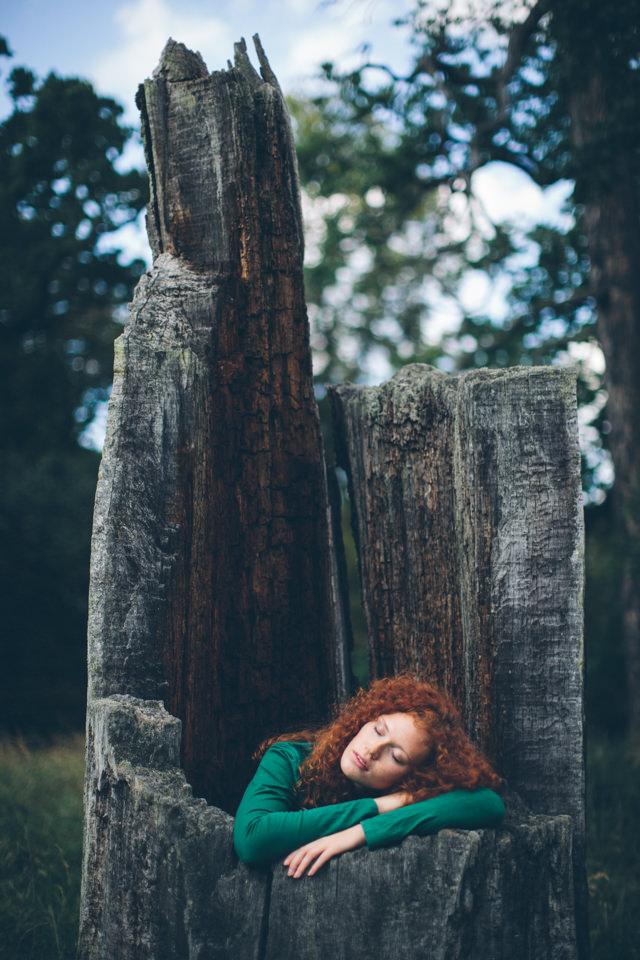 Eine Frau sitzt in einem Baumstumpf