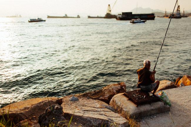 Ein alter Fischer am Wasser