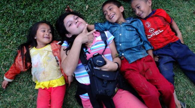 Vier Kinder liegen auf der Wiese, das größte mit Kamera um den Hals macht ein Peace-Zeichen.