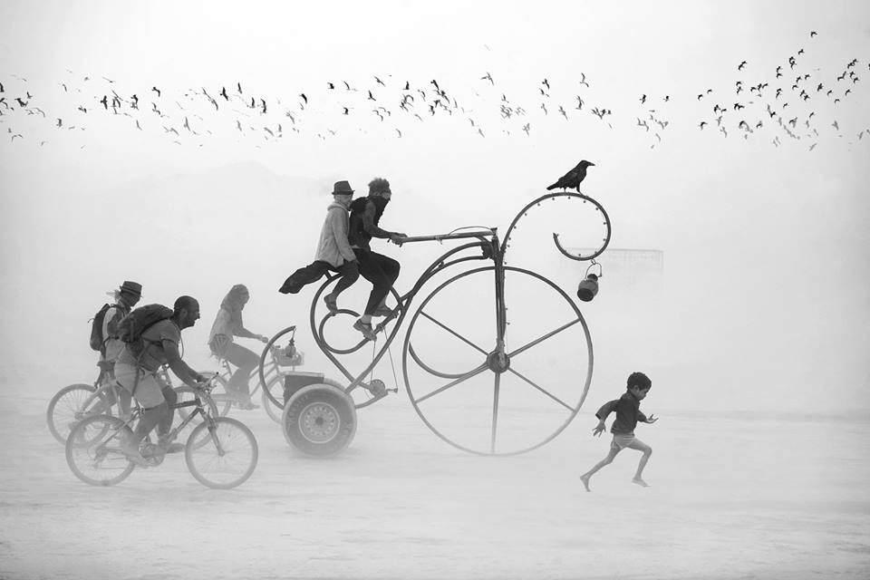 Ein seltsamen Gefährt gefolgt von drei Fahrrädern und einem kleinen Jungen in der Wüste.