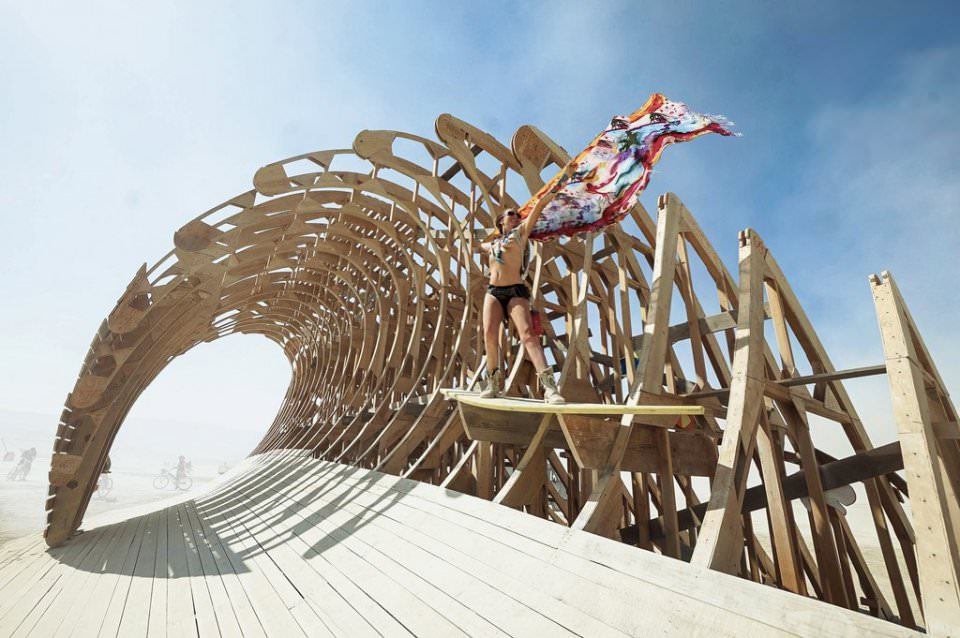 Eine Frau mit Tuch im Wind auf einem seltsamen Holzgerüst.