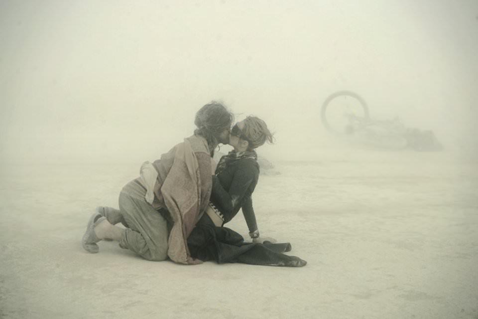 Zwei Menschen küssen sich im Wüstensand sitzend.