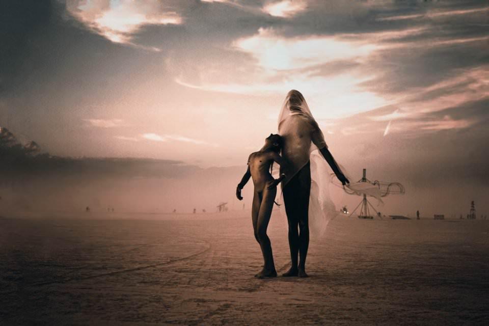 Zwei nackte Menschen vor einer Wüstenkulisse.