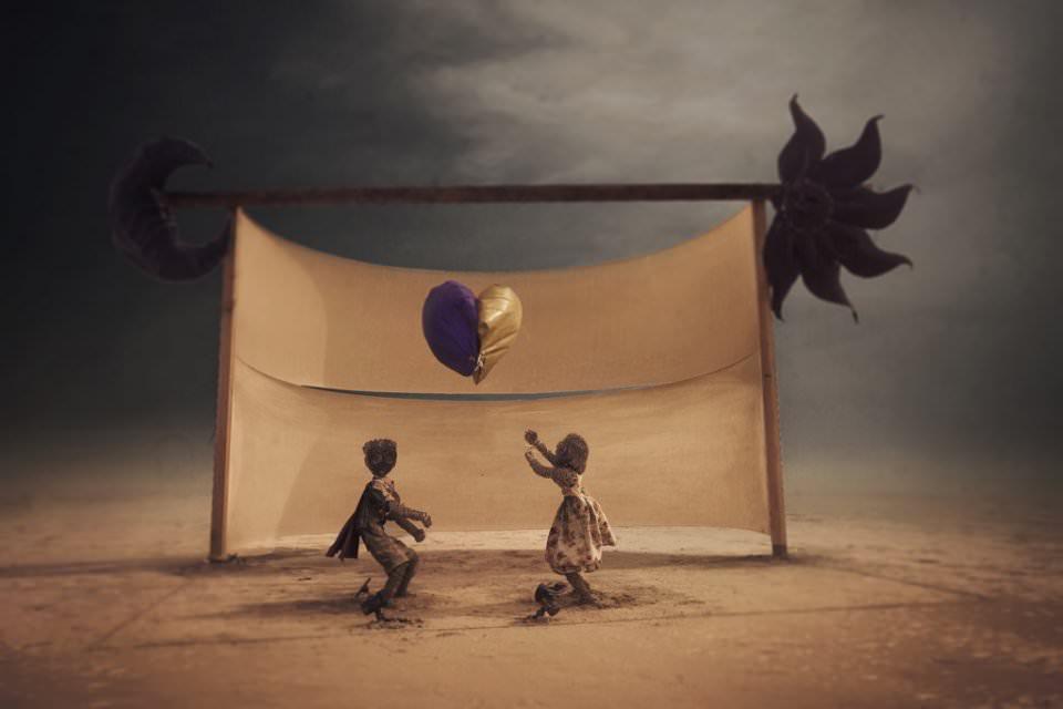 Installation mit zwei Personen, die mit einem Herzluftballon spielen.