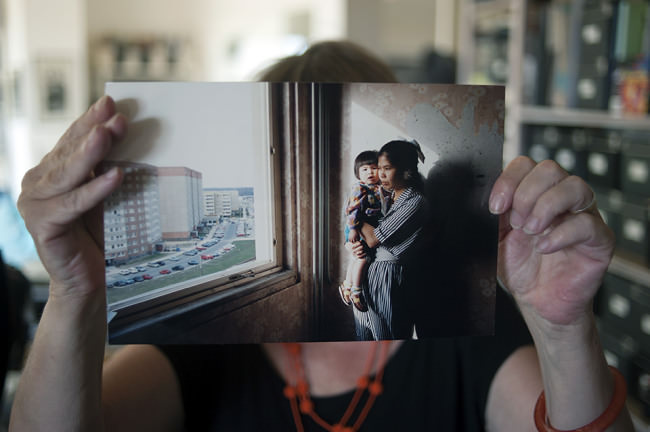 Ann-Christine Jansson zeigt einen Abzug eines Fotos von einer vietnamesischen Frau mit ihrem Kind auf dem Arm am Fenster einer Plattenbauwohnung.