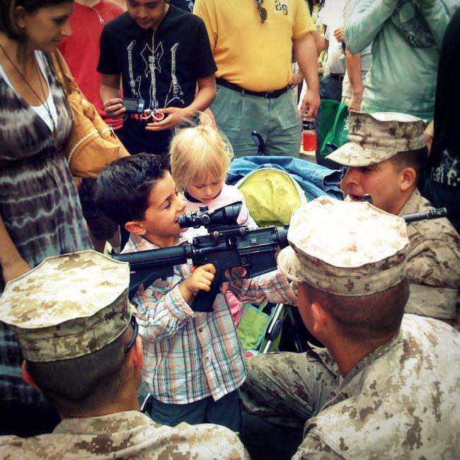Straßenfotografie: Kinder sind umringt von Soldaten uns ein Junge hält eine Maschinenpistole in der Hand.
