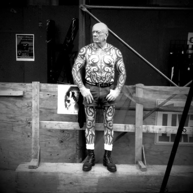 Straßenfotografie: Ein deutlich tätowierter Mann mit nacktem Oberkörper schaut in die Kamera.
