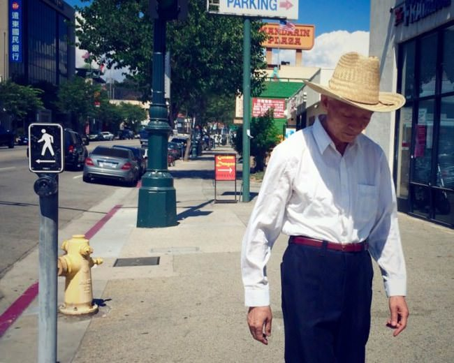 Straßenfotografie: Ein Mann mit Cowboyhut läuft vorbei.