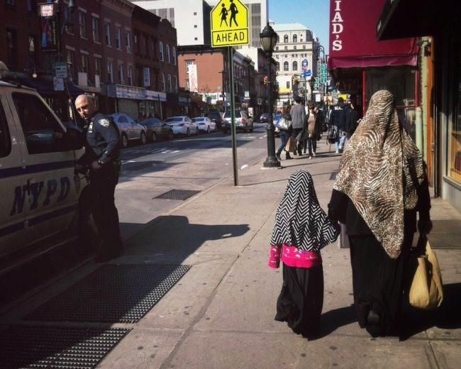 Straßenfotografie: EIne Frau läuft mit ihrere Tochter an einem Auto vorbei.