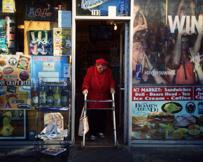 Straßenfotografie: Eine ältere Frau läuft durch einen Ladenausgang.