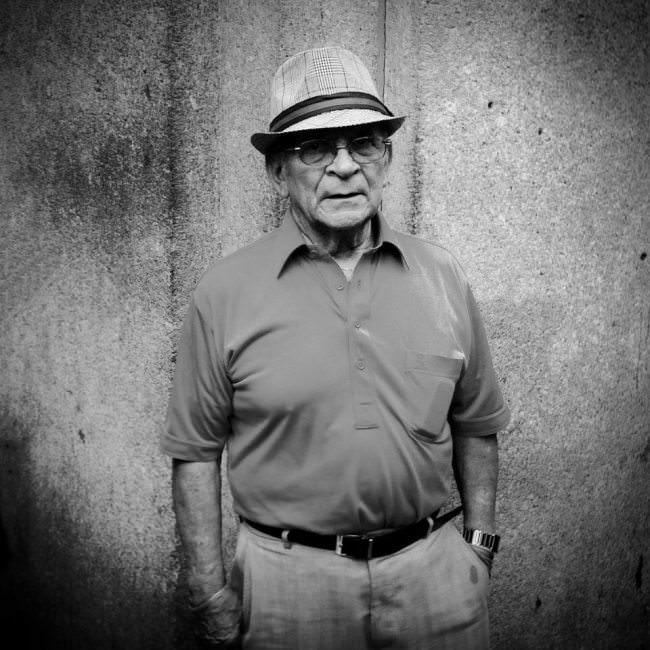 Straßenfotografie: Ein älterer Mann mit Hut vor einer Wand. Schwarzweiß-Foto.