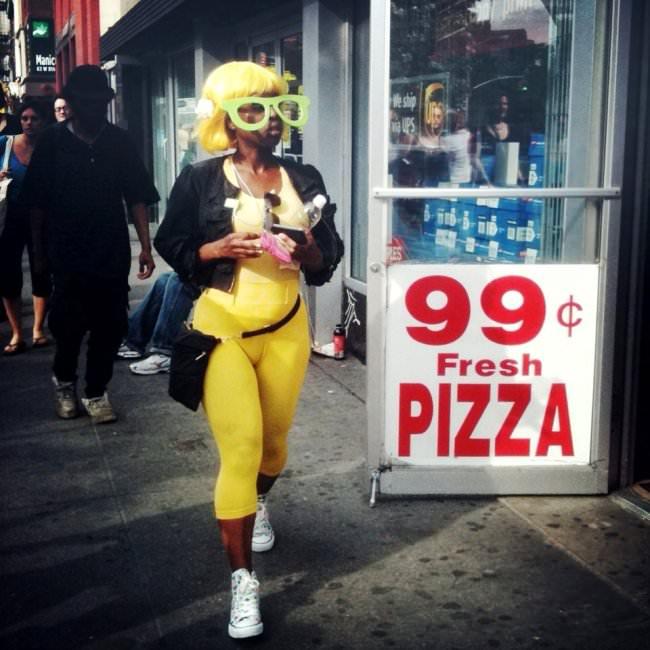 Straßenfotografie: Eine Frau mit gelber Riesenbrille auf dem Gehweg.
