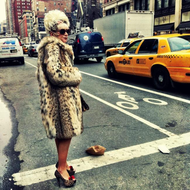 Straßenfotografie: Eine Frau im Pelzmantel steht am Straßenrand.