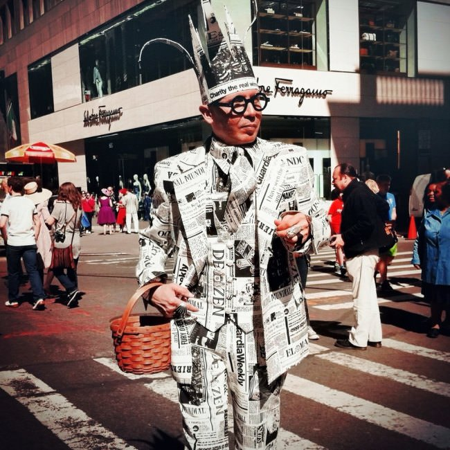 Straßenfotografie: Ein in Zeitungen gekleideter Mann steht auf einem Zebrastreifen.