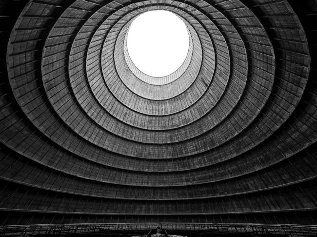 Grauer ringförmiger Tunnel mit kreisrunder heller Öffnung.