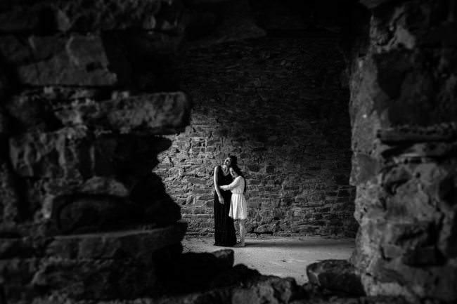 Zwei Frauen umarmen sich in einem alten Gemäuer.