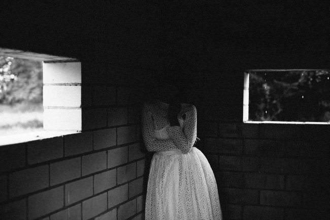 Eine Frau im weißen Kleid in einer Ecke eines Gebäudes. Ihr Gesicht verschwindet in der Dunkelheit.