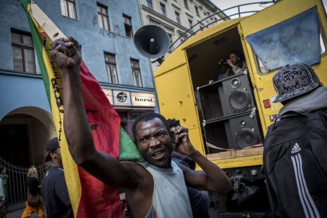 Auf einer Demonstration hält ein Mann eine Flagge in der Hand.