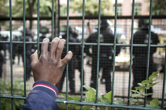 Eine Hand, ein Zaun und Polizei in kompletter Montur mit Schlagstöcken.