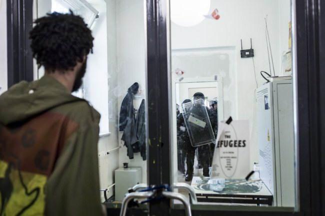 In der Schule stehen sich Flüchtlinge und Polizisten gegenüber.