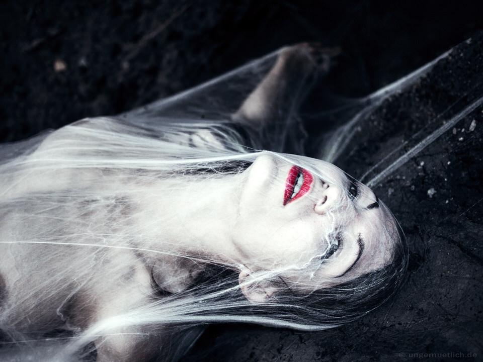 Eine Frau, von Spinnweben bedeckt.