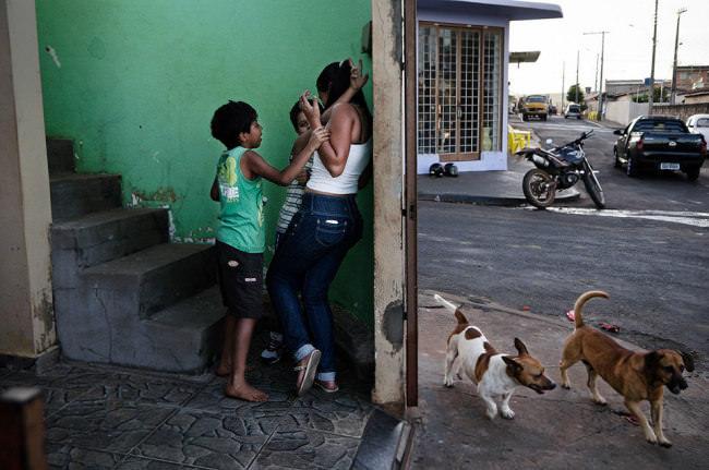Zwei Jungs bedrängen eine Frau in einem Treppenhaus, daneben laufen draußen zwei Hunde um die Straßenecke.