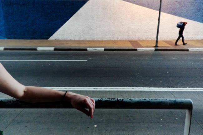 Auf dem Gehweg einer sonst leeren Straße geht ein Mann vorbei, im Vordergrund liegt der Arm einer Frau auf einem Geländer.