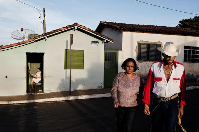 Ein Paar vor zwei Häusern, in einer Türöffnung sitzt eine weitere Frau.