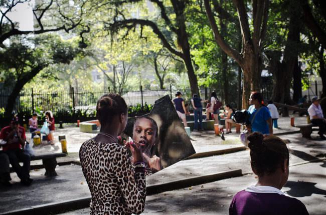 Auf der Straße schminkt sich eine Frau in einer großen Spiegelfliese, die sie in der Hand hält.