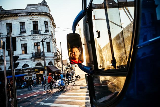 Über den Spiegel seines Fahrzeugs schaut ein Busfahrer direkt in die Kamera.