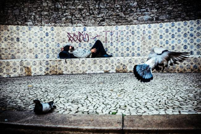 Auf einem gefliesten Platz liegt ein Mann und döst, im Vordergrund zwei Tauben.