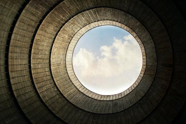 Ein graues kreisrundes Gebilde gibt an der Öffnung einen Blick auf die Wolken frei.
